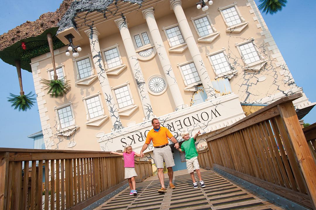 family walking outside of Wonderworks built to look like upside down building